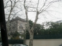 Blurred by the motion of the van, a fancy house in an elite neighborhood in Montevideo