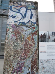 A part of the Berlin Wall covered in wads of gum and defiance